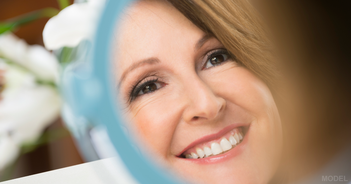 Woman with Perfect Teeth Smiling in Small Mirror