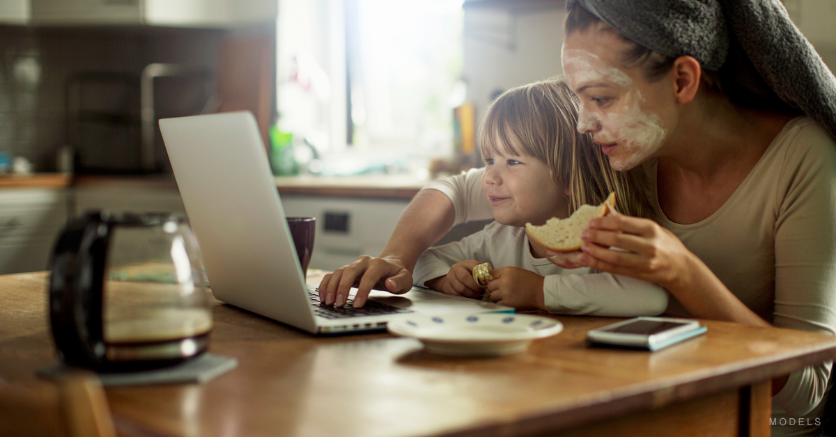 A mother and her child browse the web while eating a snack.